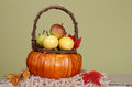 Pumpkins and apples in baskets on wood bench weave orange decorated with flowers fall leaves rustic againt light green Stock Photography