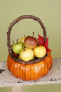 Pumpkins and apples in baskets on wood bench weave orange decorated with flowers fall leaves rustic againt light green Stock Photo