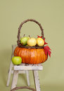 Pumpkins and apples in baskets on wood bench weave orange decorated with flowers fall leaves rustic againt light green Royalty Free Stock Image