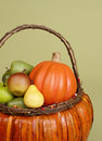 Pumpkins and apples in baskets on wood bench weave orange decorated with flowers fall leaves rustic againt light green Stock Images