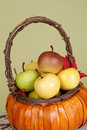 Pumpkins and apples in baskets on wood bench weave orange decorated with flowers fall leaves rustic againt light green Stock Image