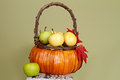 Pumpkins and apples in baskets on wood bench weave orange decorated with flowers fall leaves rustic againt light green Royalty Free Stock Photos