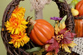 Pumpkins and apples in baskets on wood bench weave orange decorated with flowers fall leaves rustic againt light green Royalty Free Stock Photography