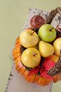 Pumpkins and apples in baskets on wood bench weave orange decorated with flowers fall leaves rustic againt light green Stock Photos