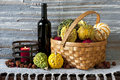 Pumpkins in basket with bottle of red wine and candle on texture background Stock Photography