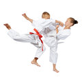 Punch in the jump and kick leg are beating the sportsmens in karategi Royalty Free Stock Photo