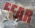 Punching, break concrete wall with word fear on it and small pie Royalty Free Stock Photo