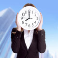 Punctual office worker concept business woman wearing formal suit and holding big clock on face standing outdoors on building Royalty Free Stock Photography