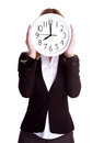 Punctual worker concept business woman wearing formal suit and holding big clock on face isolated on white background Stock Photo