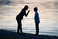 Punishing her son a mother is in the evening on the beach of a lake Royalty Free Stock Image