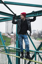 Punk guy standing on a bridge with beanie Stock Photos