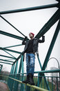 Punk guy standing on a bridge with beanie Stock Photo