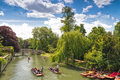 Punting canals cambridge england four boats full of people being pushed down one of s by punters with poles on a beautiful sunny Stock Image