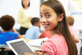 Pupil in class using digital tablet sitting at desk smiling to camera Royalty Free Stock Photo