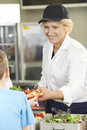 Pupil In School Cafeteria Being Served Lunch By Dinner Lady Royalty Free Stock Photo