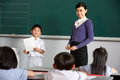 Pupil And Teacher By Blackboard In Chinese Class Stock Photo