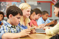 Pupils in class using digital tablet with teacher and blond female pupil smiling at the Royalty Free Stock Photos
