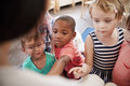 Pupils At Montessori School Looking At Book With Teacher Royalty Free Stock Photo