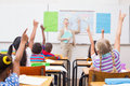 Pupils raising hand during geography lesson in classroom Royalty Free Stock Photo
