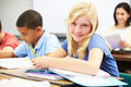Pupils studying at desks in classroom writing book sitting down Stock Photography