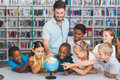 Pupils and teacher looking at globe in library Royalty Free Stock Photo