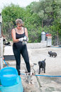 Puppies young woman cleaning feeding bowls at a dog sanctuary Stock Images