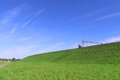 Pure blue sky, bright green lawn and road on hill Royalty Free Stock Photo