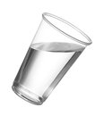 Pure drinking water in disposable plastic cup or glass with starting to spill over edge of pint glass Royalty Free Stock Photography