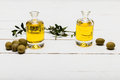 Pure olive oil and green olives on wooden surface Royalty Free Stock Photo