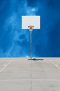 Pure white basketball standard or backboard with cloudy background orange rim and net on a gray concrete surface a blue Stock Images