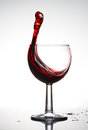 Pure wineglass with wave of brightly red wine on white background Royalty Free Stock Photo