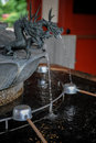 Purification fountain with sculpted dragon head at a shrine Royalty Free Stock Images