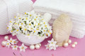 Purity jasmine flowers with buddha pearls and white bathroom accessories over mottled lilac background Royalty Free Stock Photos