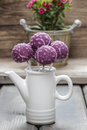 Purple cake pops in white ceramic pot on wooden background party dessert Royalty Free Stock Photos