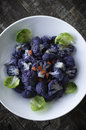 Purple cauliflower white bowl with roasted with brussels sprouts petals and red chili peppers Stock Images