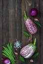 Purple eggplant, garlic and basil leaves from above on the old wooden board with free text space. Fresh harvest from the garden. T Royalty Free Stock Photo