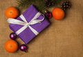 Purple gift with white ribbon and Christmas decorations Royalty Free Stock Photo