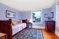 Purple guest bedroom with single wood bed and blue rug. Royalty Free Stock Photo