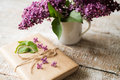 Purple lilac bouquet in vase and present laid on wooden table. Royalty Free Stock Photo