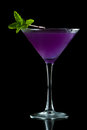 Purple martini refreshing served on a black background garnished with fresh mint Stock Images