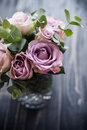 Purple, mauve color fresh summer roses in vase with black tablet Royalty Free Stock Photo