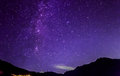Purple night sky stars. Milky way across mountains Royalty Free Stock Photo