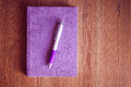 Purple notebook and pen on wooden table Royalty Free Stock Photo