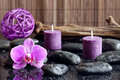 Purple orchid candles and zen stones spa concept Royalty Free Stock Photo
