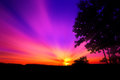 Purple and red sunset with rays of sun that stretch in the sky Royalty Free Stock Photography