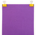Purple sheet of paper with yellow paper clip on a white backgrou