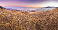 Purple sunset in mountains above the sea panorama of with grass on hill Royalty Free Stock Photo