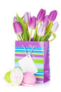 Purple tulip bouquet in gift bag and easter eggs Royalty Free Stock Photo