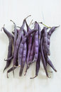 Purple wax snap bean bunch of beans on white rustic board in vertical format Stock Image