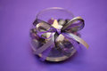 Purple wedding table decoration centerpiece a of a glass bowl with polished rocks and a ribbon bow a candle sits inside the glass Royalty Free Stock Image